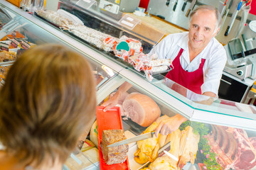 Butcher serving customer with pate