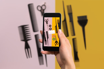 Female hand with a smartphone makes a photo set of combs on pink and yellow background