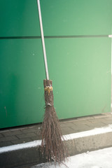 Old wicked broom at the green wall . witch's broomstick.