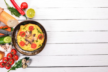 Omelette with mushrooms and fresh vegetables and nuts on a frying pan. On a wooden background. Top view. Copy space.