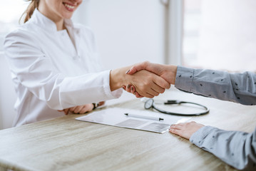 Handshake between doctor and patient. Close-up.