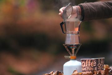 Geyser aluminium coffee maker on tourist gas cylinder outdoors in autumn season