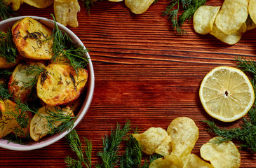 Fried potatoes with salt, dill, lemon and spices on a wooden Board on brown background with copy space. The view from the top