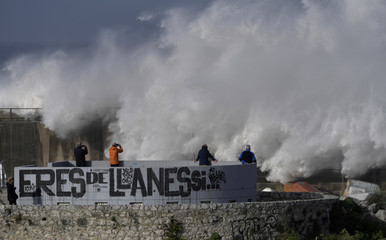 People look and take pictures of giant waves in the port town of Llanes