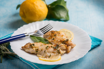 fish fillet with lemon and sage, selective focus