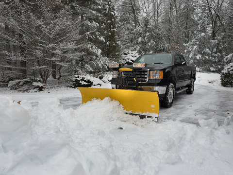 snow plow clearing a parking lot after  storm