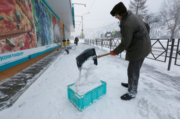 A worker removes snow from the sidewalk in front of a grocery store on a frosty winter day in the Siberian town of Divnogorsk