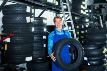 man working with new tyre for car