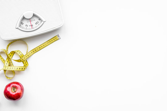Lose weight concept. Scale and measuring tape on white background top view copy space