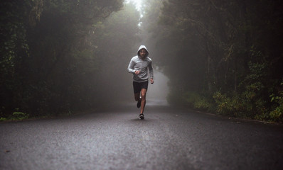 Photo sur Plexiglas Artiste KB Portrait of a young athlete running on the road