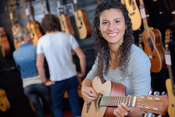 woman holding a guitar in the guitar store