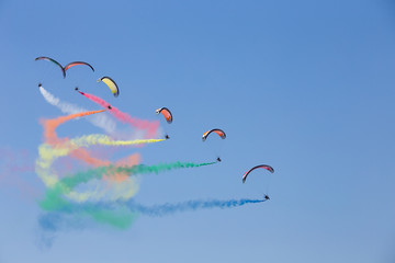 Powered parachutes Air show - multicolored Paratroopers in the sky with trail of italian flag colors over Grado beach, Italy.