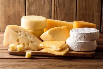 Foto auf AluDibond Milchprodukt Various types of cheese on dark rustic wooden background.