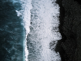 Aerial view of waves on black sand beach