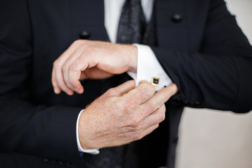 Close-up of elegance male hands wearing modern black suit