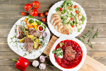 Different dishes on wooden table, top view. Vegetable beet soup, rack of lamb with fried potato, Grilled chicken Caesar salad.