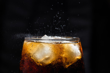 A glass of cola drink with a salt close-up.