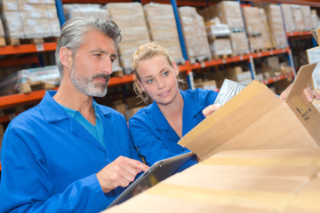Man and woman opening box in warehouse