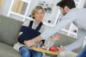 injured woman is being assisted to breakfast on sofa