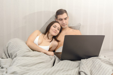 Couple pretty smile while watching the video on the laptop lying on bed in bedroom
