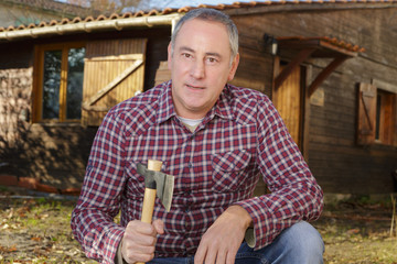 man standing near old wooden house and holding axe