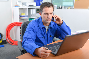 Man on telephone in front of computer