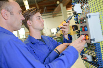 Junior and senior electricians testing circuit