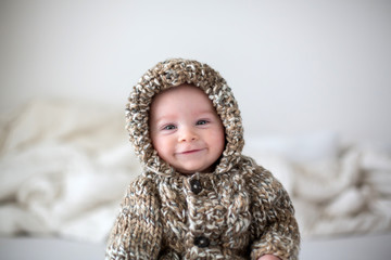 Little baby boy playing at home in bed, dressed in hand made knitted overall