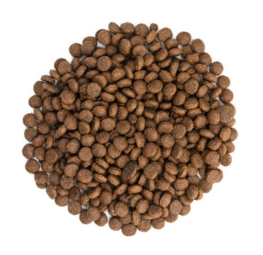 Heap of dry dog food, isolated on white background. Top view, close up.
