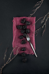 fresh ripe blackberries on a napkin and slate plate kitchen table can be used as background