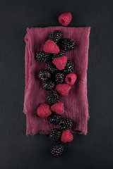 fresh ripe blackberries and raspberries on a napkin and slate plate kitchen table can be used as background