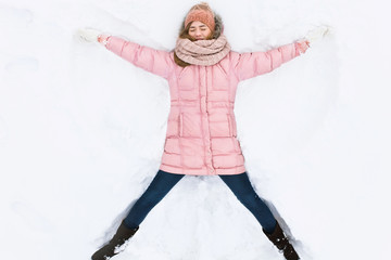 happy woman lying in the snow and moving arms and legs up and down, creating the shape of a snow angel. Smiling woman lying on snow in winter holiday ,for advertising ,