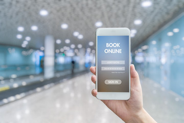 Woman hand holding smartphone against blur bokeh of airport background BOOK online concept