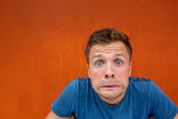 Caucasian man with funny face on red background