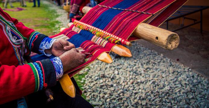 Hands weaving traditional blanket Chinchero