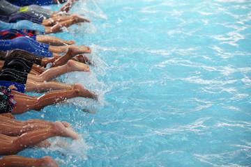 leg shot of children learning to swim in swimming pool