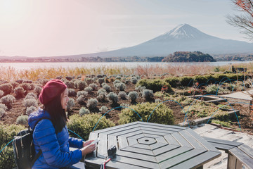 Asian beautiful woman tourists are traveling and sitting in the park with Mt Fuji in the morning on the lake kawaguchiko, Japan.