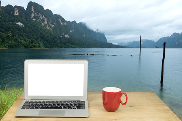 laptop and coffee mug on wood table with background workspace concept