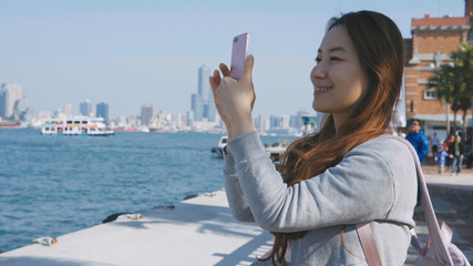Young woman traveling to Taiwan using phone to take photo