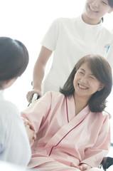 患者の手を握る女医と看護師
