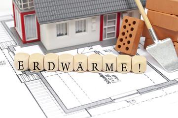 Haus mit Bauplan und Ziegelsteinen Erdwärme