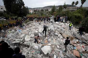 People stand on the rubble of the house of Palestinian gunman Ahmed Jarrar following an Israeli raid, in the West Bank city of Jenin