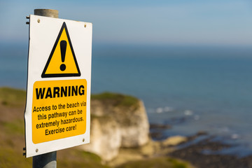 Warning sign with blurry Flamborough Head coast and cliffs in the background, near Bridlington, East Riding of Yorkshire, UK