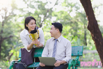 Happy asian business couple associates after receiving awards from work in the park.