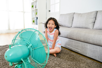 happy attractive female kid blowing cooling wind