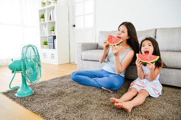 woman with little girl eating watermelon together