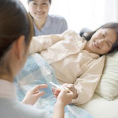患者に体温計を渡す看護師(訪問医療)