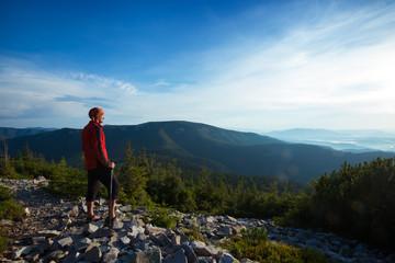 Traveler stands on a stony mountain range