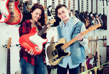 Pretty female and male teenagers examining electric guitars