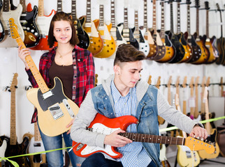 Cheerful female and male teenagers examining electric guitars